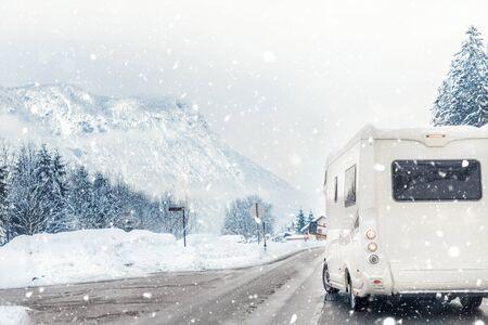 寒い冬の季節に背景に美しい山の高山の風景と道路から回るキャラバンやキャンピングカー。家族旅行、モーターホームでの休暇旅行。美しいオーストリアの自然のシーン。