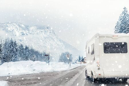 Caravan or campervan turning from road with beautiful mountain alpine landscape on background at cold winter season.Family vacation travel, holiday trip in motorhome. Beautiful austrian nature scene. Stock Photo
