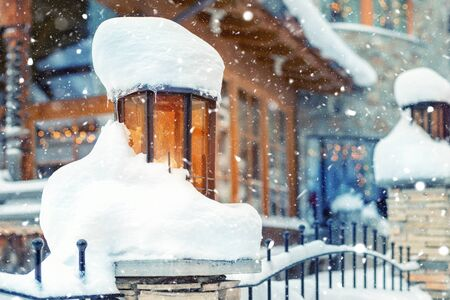 Cozy vintage street lamp with orange glass covered by snow and wooden rustic house on background outdoors at snowfall. Retro metal lantern decoration on alpine resort street. Christmas mood scene.