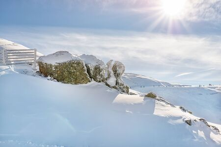 Scenic alpine mountain peak covered with thick snow layer with rocks and fence defense from avalanche on bright sunny day. Virgin snow skiing area Reklamní fotografie