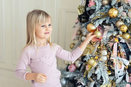 Cute adorable caucasian little blond smiling girl enjoy decorating christmas tree at home indoors. Happy child wearing pink sweater trimming new year symbol with baubles, toys and ribbon inside house Reklamní fotografie