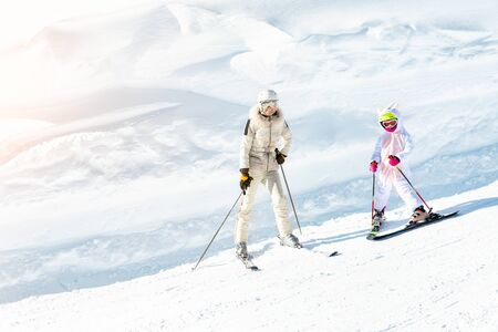 Young adult beautiful sporty mother having fun skiing with kid daughter on mountain alpine ski winter resort. Slim mom in luxury fashion skier suit and child enjoy outdoor recreation activities