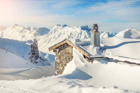 Scenic Highland alpine old abandoned stone hut with chimney snowbound by thick snow layer after blizzard. Mountain rustic shelter building landscape on bright sunny day