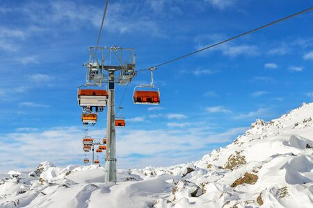 Ski lift ropeway on hilghland alpine mountain winter resort on bright sunny day. Ski chairlift cable way with people enjoy skiing and snowboarding. downhill slopes and virgin snow off-piste area. Stockfoto