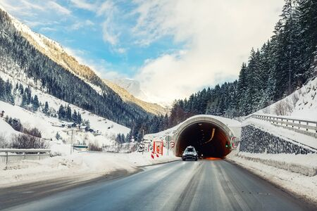 Winter alpine road landscape with tunnel, forest, mountains and blue sky on background at bright cold sunny day. Car trip family travel journey. Holiday skiing vacation. scenic austrian landscape.