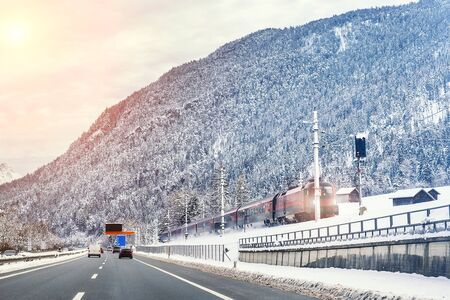 Winter alpine mountain highway and parallel railway road with intercity fast train and cloude sunset sky on background at cold day. Car trip family travel journey vacation. Transportation mode. Reklamní fotografie