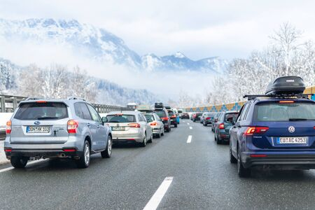 January 12th, 2019 - Salzburg, Austria: Winter highway with many different cars stucked in traffic jam due ti bad weather conditions. Vehicles on road heavy snowstorm and blizzard on cold winter day.
