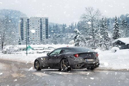 Kuffstein, Germany - Janyary 12th, 2019: Black modern Ferrari FF supercar driving along dirty mud slippery driveway at snowy winter day in European city street. Fast sport car in cold snowfall season.