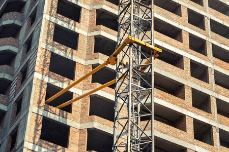 Close-up detail of highrise tower crane attached to building brick wall at hightower industrial construction site. Engineering and heavy machinery background. Reklamní fotografie