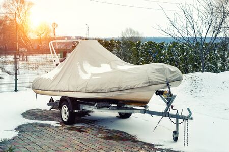 Inflatable luxury fishing motorboat wrapped in cover standing over trailer for winter period seasonal storage at backyard. Shrink-wrapped vessel winterized on parking.