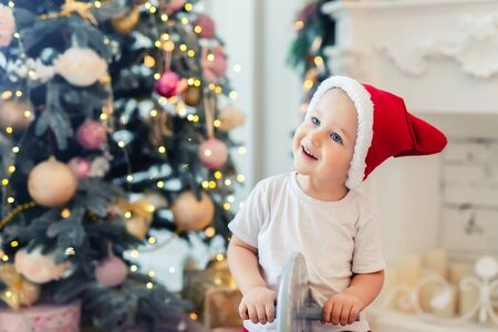 Adorable cute child boy having fun plying at home in red santa claus hat and festive christmas tree on background. Happy toddler kid looking and smiling during playing at home at new year holidays.