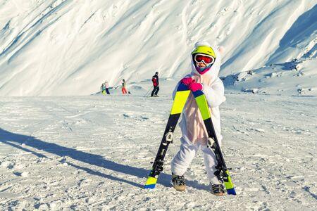 Cute adorable preschooler caucasian kid girl portrait with ski in helmet, goggles and unicorn fun costume enjoy winter sport activities. Little child skiing on luxury alpine resort in mountains. Reklamní fotografie
