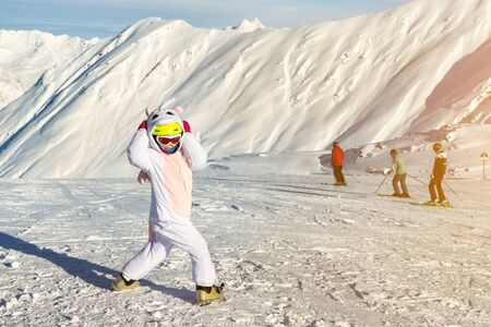 Cute adorable funny caucasian kid girl portrait in helmet, goggles and unicorn fun costume enjoy winter sport activities. Little child scared surprised or shocked expression holds hand on head