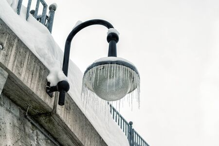 Outdoor street lantern hanged on concrete wall covered with icicles on cold winter day. Winter weather season background. Reklamní fotografie