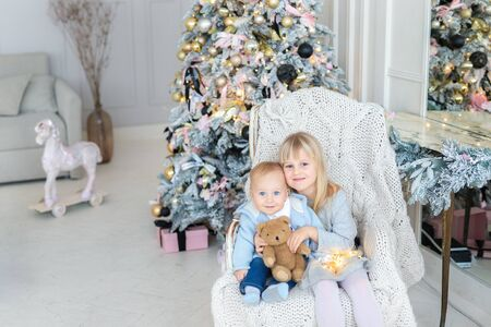Two cute adorable little siblings brother and sister sitting in chair near christmas tree in cozy living room looking , dreaming and waiting xmas wonder. Portrait of pair smiling adorable blond kids