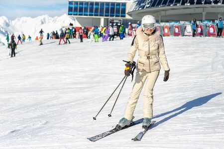 Portrait of young adult beautiful happy caucasian woman smiling near lift station at alpine winter skiing resort. Girl in fashion ski suit, goggles and white helmet. Winter sport vacation and tourism