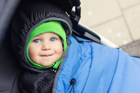 Portrait of cute caucasian toddler boy in black hooded warm insulated dawn overall jacket and blue blanket sitting in stroller and enjoy walking putdoors at cold winter day. Adorable happy child