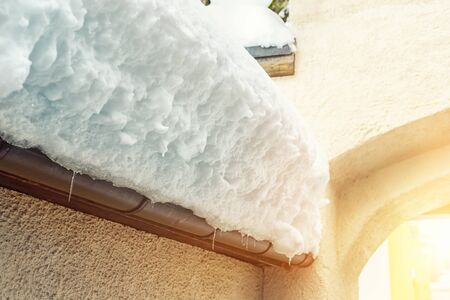 Roof of ancient stone building covered with thick snow drift layer after heavy snowfall blizzard on street of old european austrian Kufstein town. Scenic winter weather background. sun in stone arc.