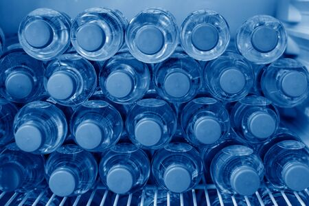 Rows of many transparent plastic bottles with drinking water supply in white refrigerator. Mineral water stack storage in fridge to drink summer day. Pantone color of the year 2020 classic blue toned.