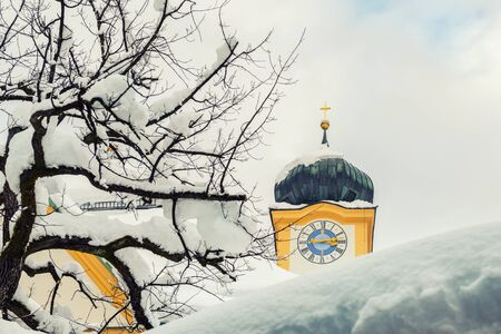 Roof of old building covered with thick snow drift layer after heavy snowfall blizzard and austrian Kufstein town. hall tower with clocks on background on bright sunny winter day winter weather scene.