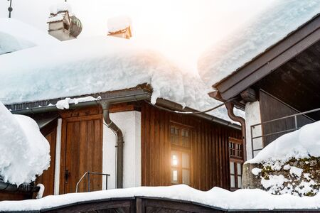 Roof of ancient wooden building covered with thick snow drift layer after heavy snowfall blizzard on street old european austrian Kufstein town. Scenic winter weather background. sun in small window.