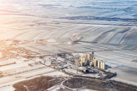 Aerial landscape view from plane of industrial cement mixing and producing plant or bionergy refinery factory.Industry facility background. Environmental pollution and garbage recycling Reklamní fotografie