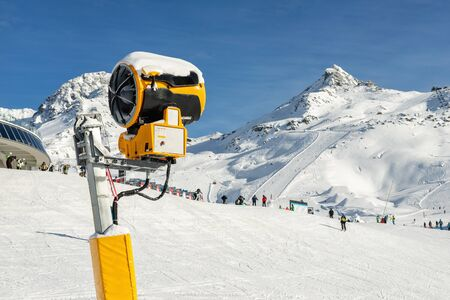 Artificial Snow cannon near piste.Ski lift ropeway on hilghland alpine mountain winter resort on bright sunny day. panoramic wide landscape view of downhill slopes with people enjoy sport activities