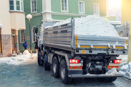 Big dump truck fully loaded with snow driving through narrow street of historical center at old european city. Heavy machinery snow removal. Municipal services cleaning and maintenance town roads.