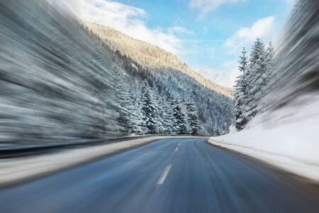 Winter alpine road curve landscape with forest, mountains and blue sky on background at bright cold sunny day. Car trip family travel journey. Holiday skiing vacation. scenic austrian landscape.