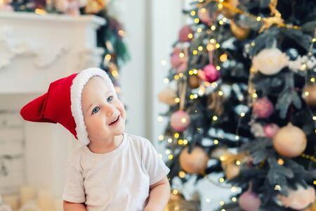 Adorable cute child boy having fun playing at home in red santa claus hat and festive christmas tree on background. Happy toddler kid looking ,smiling and dreaming for holiday gift, wonder an miracle
