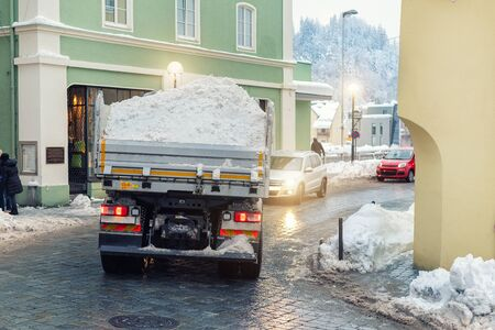Big dump truck fully loaded with snow driving by narrow street of historical center at old european city. Heavy machinery snow removal. Municipal services cleaning and maintenance town roads. Reklamní fotografie
