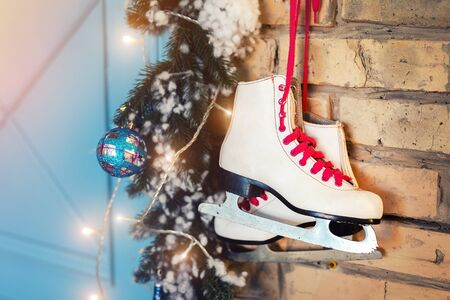 Pair of white vintage leather skates with red laces hanging on old rustic brick wall with garland lights on christmas tree decoration. Cozy scenic christmas card interior winter holidays background Reklamní fotografie