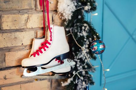 Pair of white vintage leather skates with red laces hanging on old rustic brick wall with garland lights on christmas tree decoration. Cozy scenic christmas card interior winter holidays background.