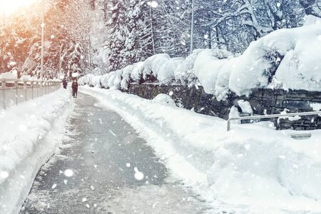 Scenic winter sidewalk park alley between snow-capped trees and bushes with clean road during frosty heavy snowfall. Snow removal on city streets. Cold weather forecast. People walking outdoors. Reklamní fotografie