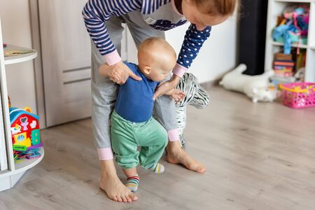 Cute little adorable blond toddler boy making first steps with mother support in playroom at home. Happy funny child learning to walk with mom help indoors.