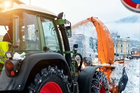 Big tractor with chains on wheel blowing snow from city street into dump truck body with snowblower. Cleaning streets and snow removal after snowfall. Municipal services snow removal at winter season
