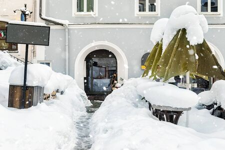European city street snowcapped after blizzard snowfall. Outdoor cafe tables and umbrellas covered with heavy snow layer. Emty urban cityscape with bad christmas weather Reklamní fotografie