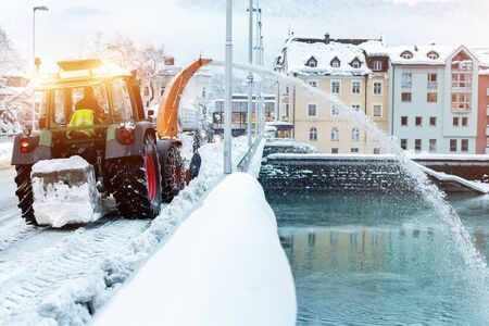 Heavy municipal services machinery removing snow from city streets. Big tractor snowblower blowing snow from bridge road into river. Cleaning streets and snow removal after snowfall at winter season.