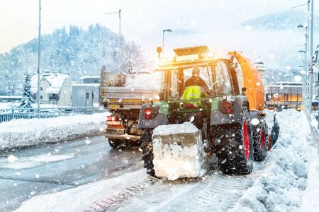 Big tractor with chains on wheel blowing snow from city street into dump truck body with snowblower. Cleaning streets and snow removal after snowfall. Municipal services snow removal at winter season. Reklamní fotografie
