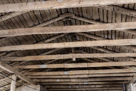 aged brown wooden timber beam on roof ceiling inside old farm or ranch building interior. Rural gabled roof old weathered abandoned bar in village