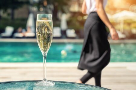 Close-up white champagne or prosecco glass against poolside at luxury resort hotel during vacation. Sparkling wine with rising bubbles with blue pool background outdoor. Waiter in black skirt leaving