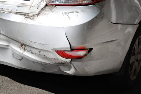 Close-up wrecked rear bumper and tail lights of new modern grey car after vehicle accident on road at bright sunny day. Stock Photo