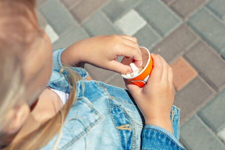 Close-up little caucasian blond kid girl girl in jeans jacket eating white sweet mini marshmallows from paper cup walking outdoor. Unhealthy junk food and children obesity cause Reklamní fotografie