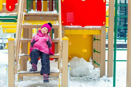 Cute adorable caucasian blond little kid girl having fun enjoy sitting on stairs at children playground covered with snow at cold winter day. Outdoors kid winter sport activities