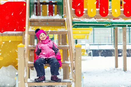 Cute adorable caucasian blond little kid girl having fun enjoy sitting on stairs at children playground covered with snow at cold winter day. Outdoors kid winter sport activities.White snowlakes