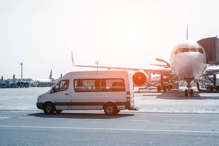 White VIP service van running on airport taxiway with big passenger airplane on background. Business class service at airport. Security intelligence agency hurrying at airfield.
