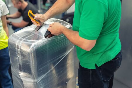 Worker wrapping suitcase with transparent protection film atairport deparure terminal before flight. Luggage protection and safety service