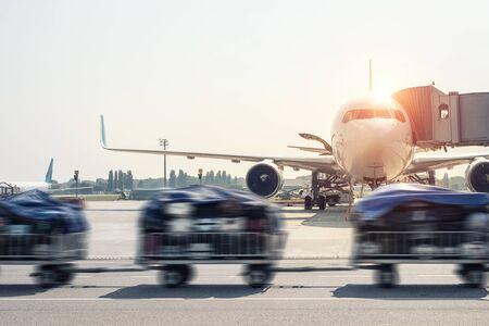 Il movimento dei bagagli ha offuscato il carrello del carrello che va veloce consegnando i bagagli dei passeggeri all'aereo moderno sulla pista di rullaggio all'aeroporto in una luminosa giornata di sole. Aerei commerciali sullo sfondo al tramonto o all'alba
