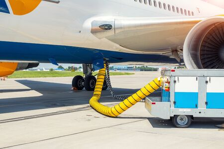 Big modern commercial plane parked on airport runway and connected to ground supply power unit. Aircraft maintenance service and check-up before flight. Airport handling industry.