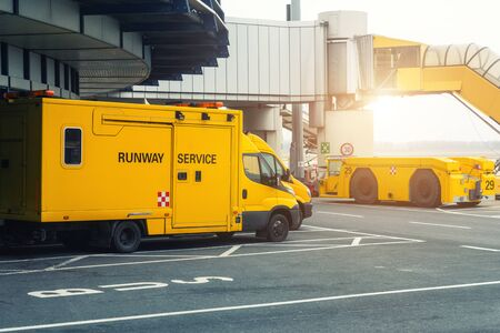 Runway service vehicles standing on tarmac near airport terminal building. Special maintenance crew truck van and tow tractor parked at marked place parking. Emergency and support equipment airfield.